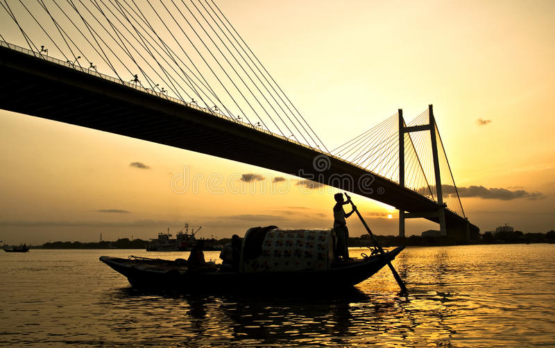 Man on a boat at the sunset. Man on a boat at sunset under bridge royalty free stock images