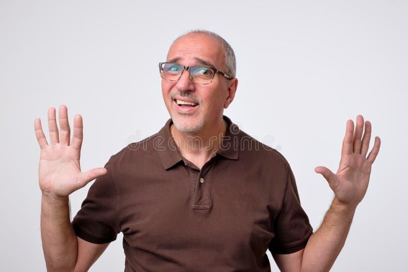 Man body language. I did not do it concept. Mature italian handsome man raising hands up. stock photos