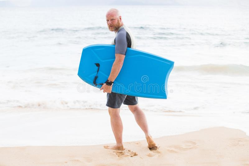 Man with boogie board at the beach. Man on boogie board in the ocean royalty free stock image