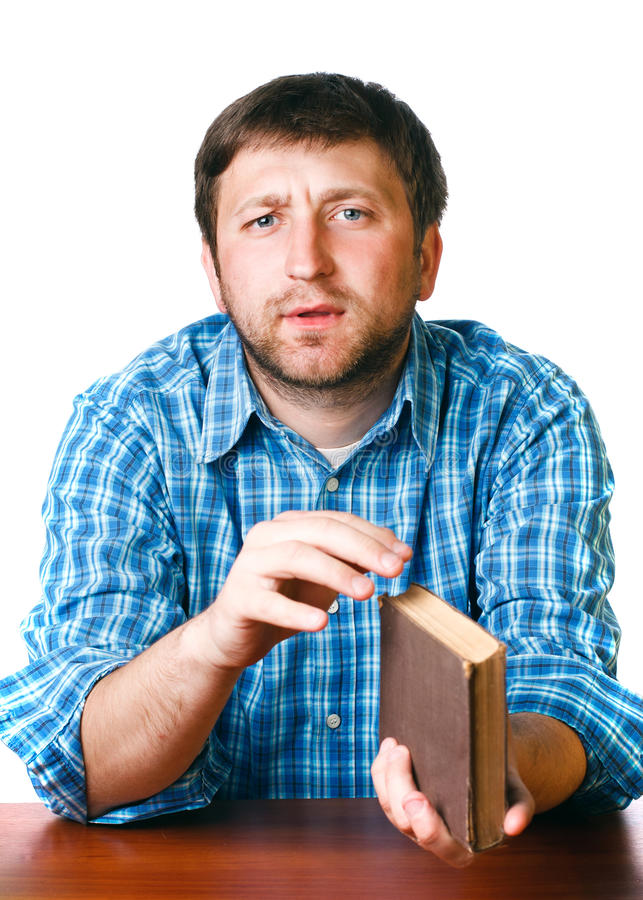 Man with a book in his hands at the table. On a white background stock photo