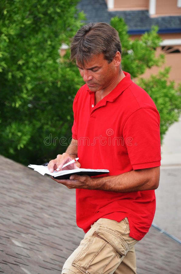 A man with a book on a roof. An insurance adjuster writing his estimate in his pad stock photography
