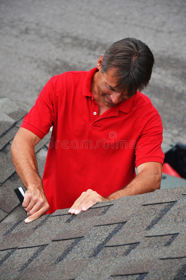 A man with a book on a roof. An insurance adjuster writing his estimate in his pad stock image
