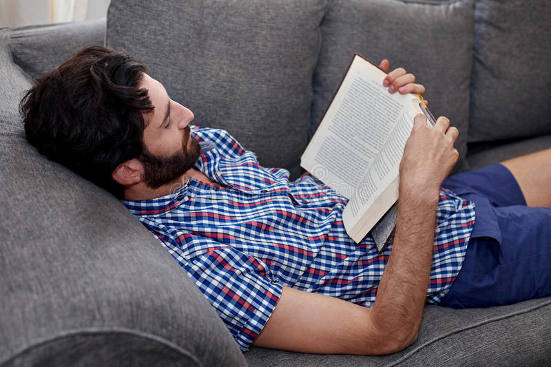 Man book sofa couch. Man relaxing on sofa couch reading literature novel story book at home living room lounge royalty free stock photography