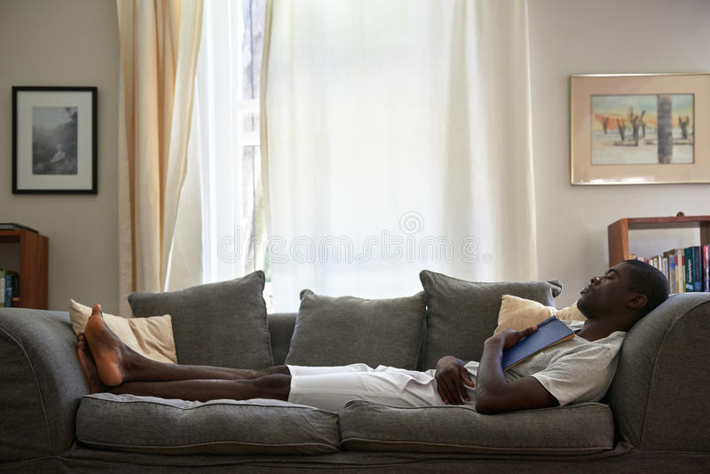 Man book sofa couch sleeping. African black man sleeping on sofa couch while reading book at home living room lounge royalty free stock photography