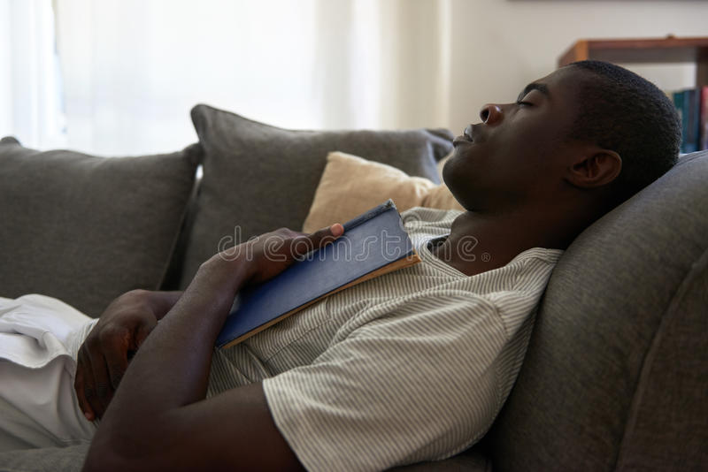 Man book sofa couch sleeping. African black man sleeping on sofa couch while reading book at home living room lounge royalty free stock photo