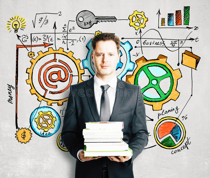 Man with books and business diagram drawn on concrete wall royalty free stock images