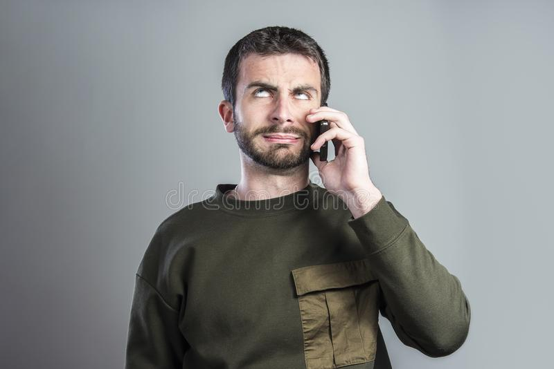 Man bored with phone conversation. Bored and frustrated man having a dull conversation over his cell phone royalty free stock photos