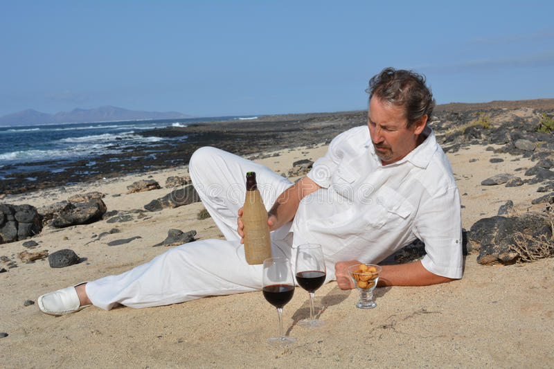 A man with a bottle of wine and glasses on the beach.Celebration. stock photography