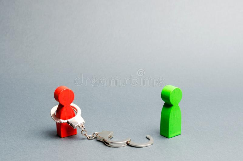 A man is bound by handcuffs standing near a free person. Exemption from debt or physical slavery. Parting or divorce of two royalty free stock photos