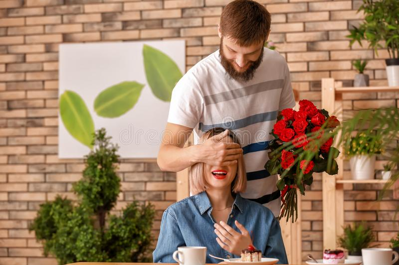 Man with bouquet of beautiful flowers covering his girlfriend's eyes in cafe royalty free stock photo
