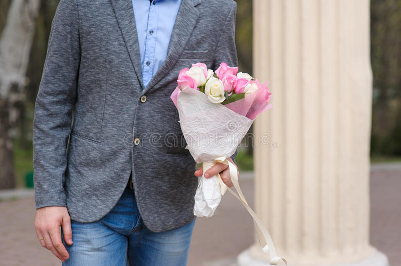 Man with bouquet of flowers waiting for a woman. Handsome with bouquet of roses man waiting a woman. bouquet of white and pink roses wrapped in paper. A man royalty free stock image