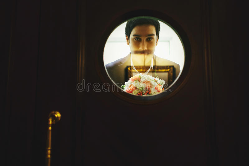 Man with a bouquet of roses looks through the round window in a. Wooden door stock image