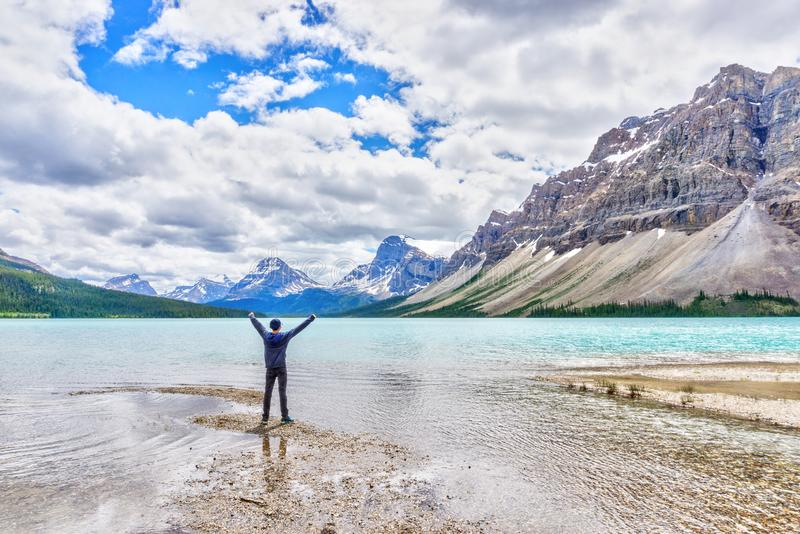 Man at Bow Lake With Crowfoot Glacier and Crowfoot Mountain stock photos