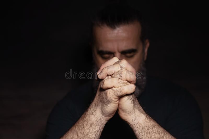 Man bowing his head in prayer with clasped hands in front of his face. In dark room stock photos