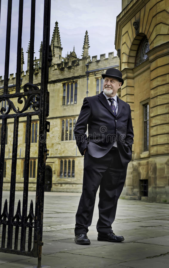 Man in Bowler Hat, Oxford, England. A man stands in front of a college at Oxford University in England wearing a bowler hat, the classic hat of British stock images