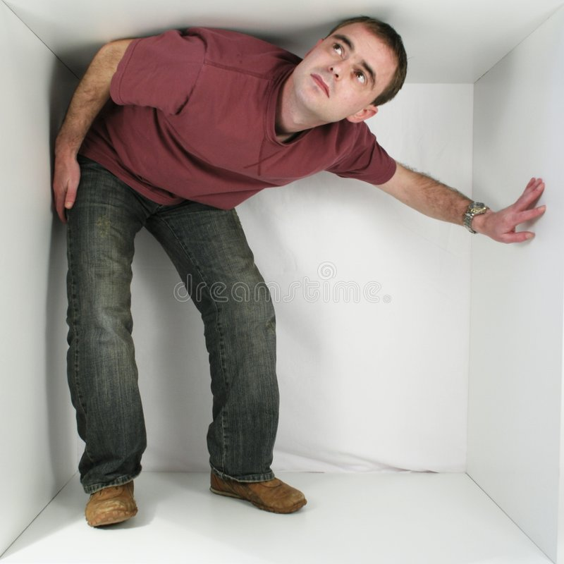 Man in a box. Casual dressed man in a white box royalty free stock image