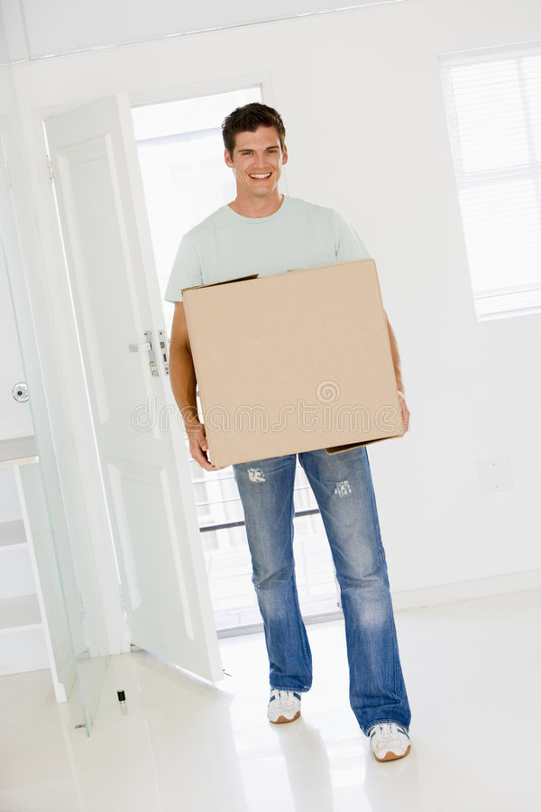 Man with box moving into new home smiling stock image