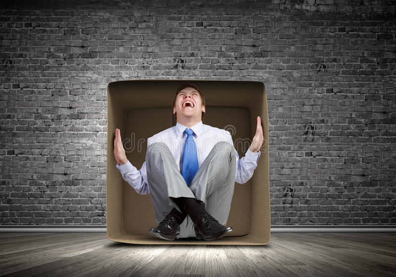 Man in box. Young frustrated businessman sitting in small carton box royalty free stock photo