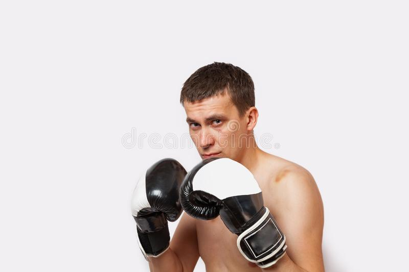 A man in boxing gloves with bruises on body and face stands in a rack during a fight and boxing on a white isolated background royalty free stock images