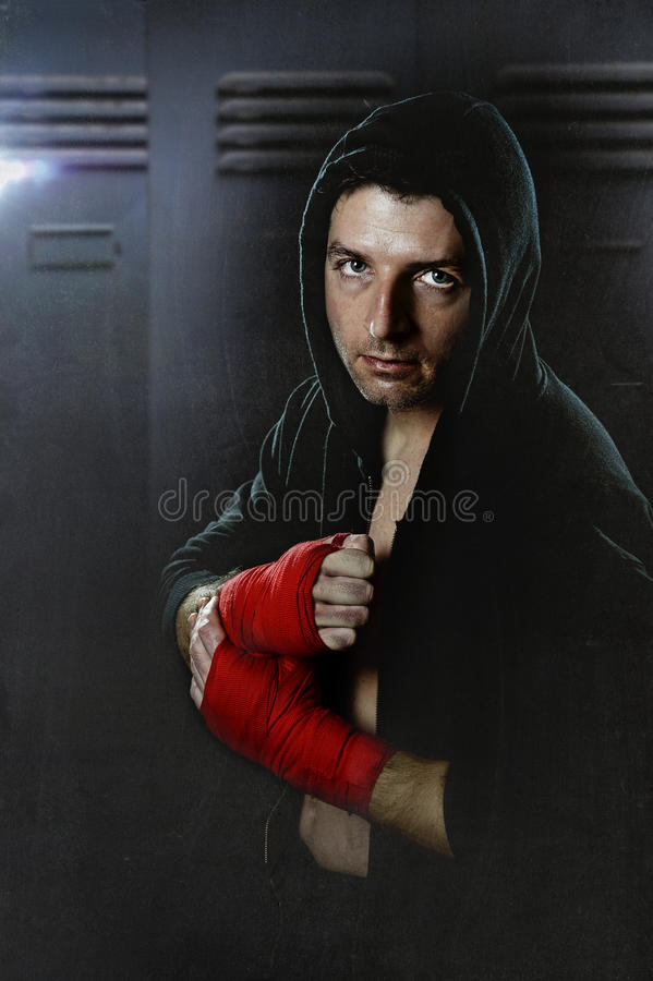 Man in boxing hoodie jumper with hood on head wearing hand and wrist wrapped ready for fighting. Young man in boxing hoodie jumper with hood on head wearing hand royalty free stock images