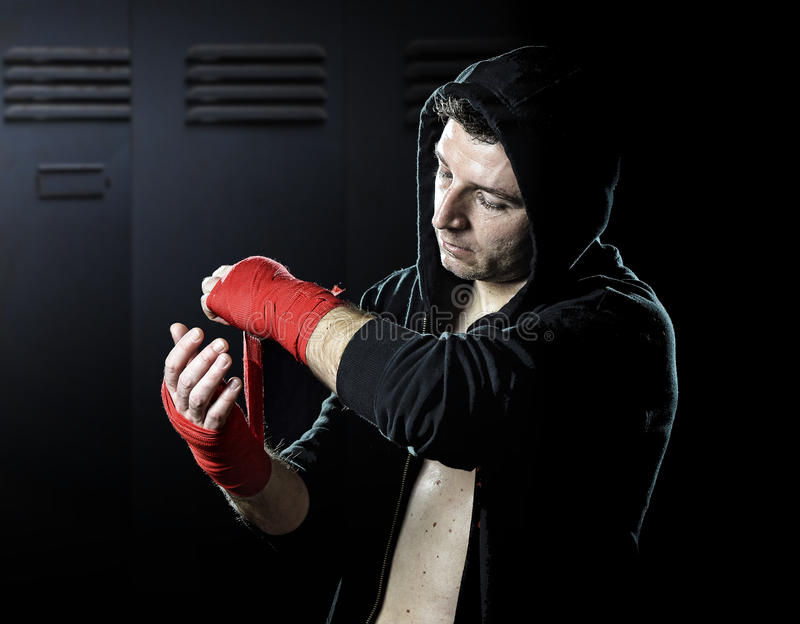 Man in boxing hoodie jumper with hood on head wrapping hands and wrists getting ready for fighting. Young man in boxing hoodie jumper with hood on head wrapping stock photography