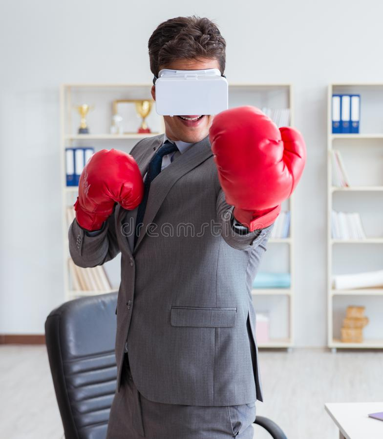 Man boxing in the office with virtual reality goggles. The man boxing in the office with virtual reality goggles royalty free stock photo