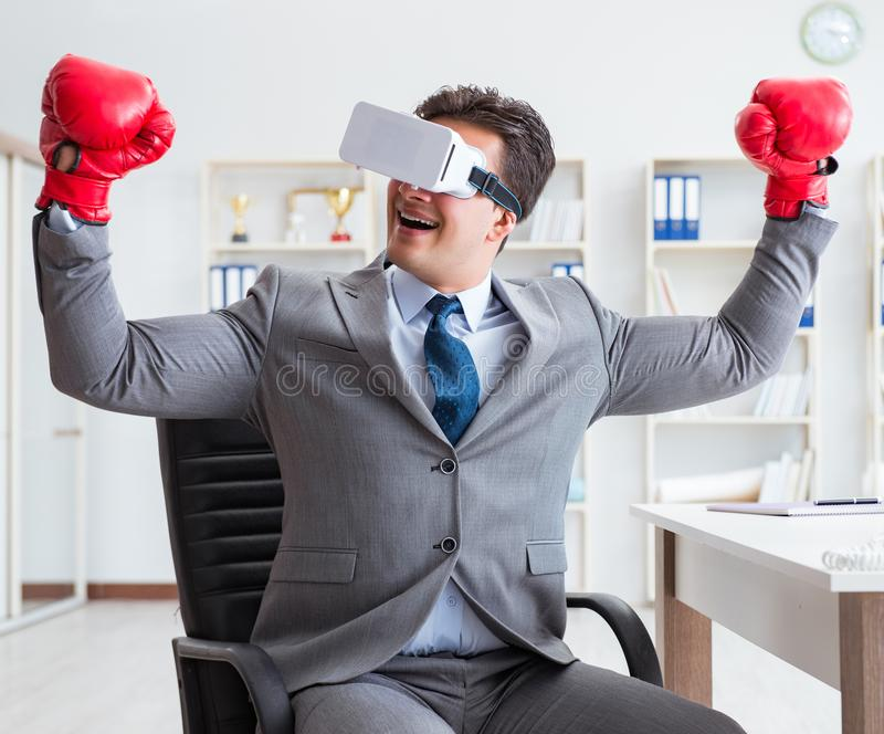 Man boxing in the office with virtual reality goggles stock photos