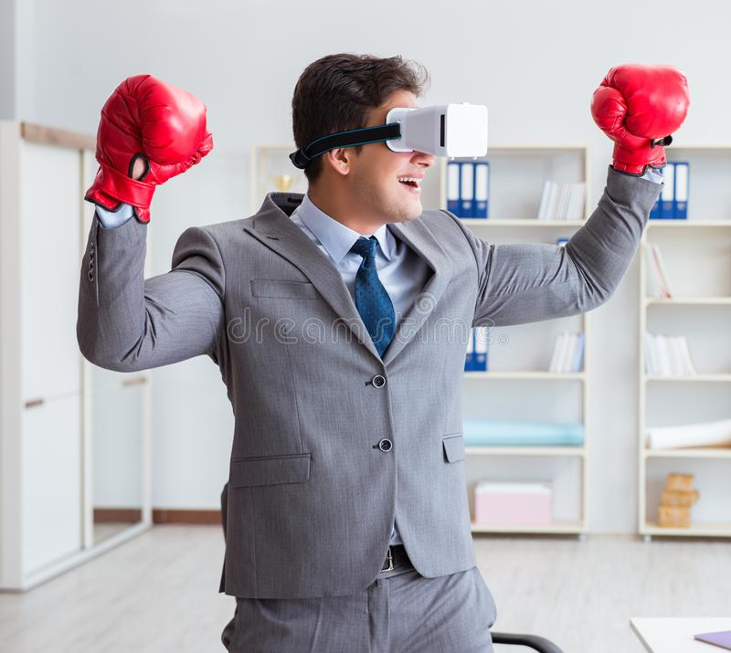 Man boxing in the office with virtual reality goggles royalty free stock images