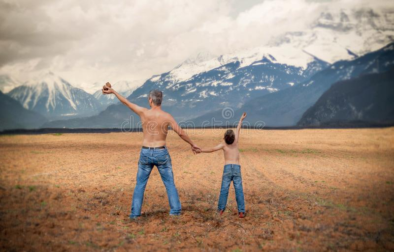 Man and a Boy in Blue Denim Jeans Standing in Brown Open Space Near White and Gray Snowy Mountains during Daytime royalty free stock photo