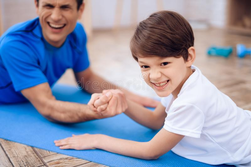 The man and the boy are engaged in arm-wrestling. The men and the boy are engaged in arm-wrestling. This is father and son. They are at home stock images