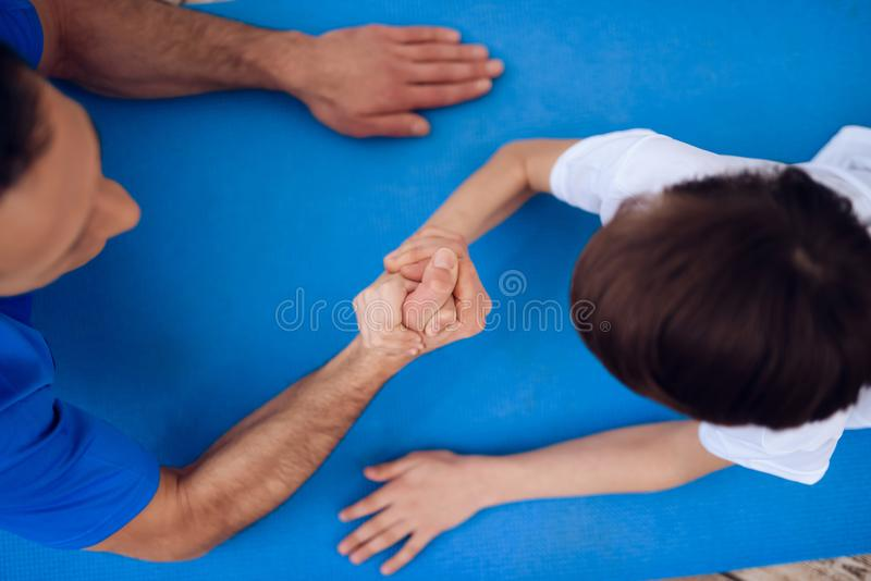 The man and the boy are engaged in arm-wrestling. The men and the boy are engaged in arm-wrestling. This is father and son. They are at home royalty free stock images