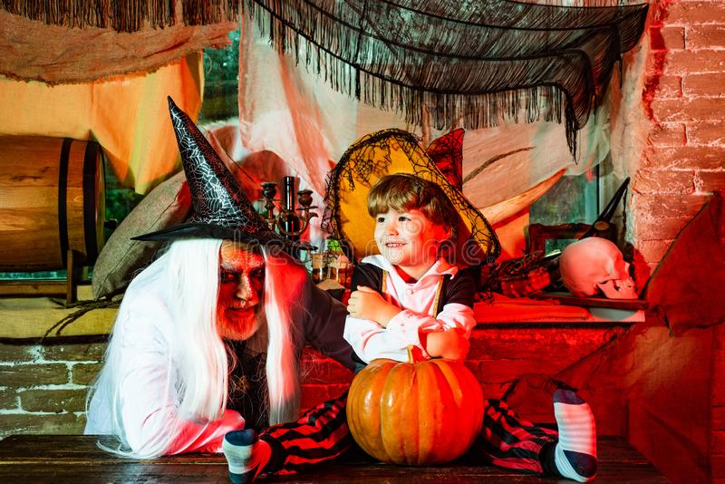 Man and boy scare guests. Happy family father and child in costumes on a celebration of Halloween. Man and boy scare guests. Happy family father and child in stock photos