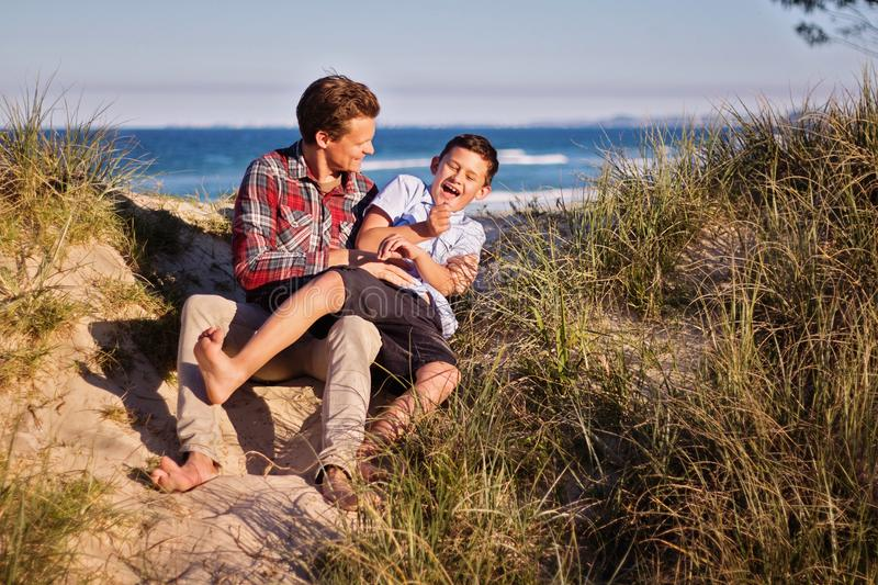 Man and Boy Sitting on Floor Near Body of Water royalty free stock image
