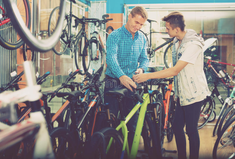 Man and boy teenager shopping new bicycle in sport shop. Smiling men and boy teenager shopping new bicycle in sport shop stock images