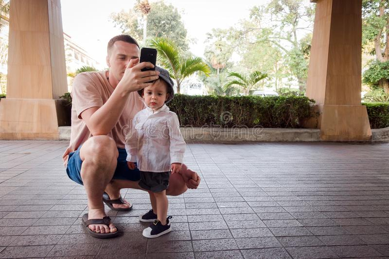 Man with boy using phone stock photography