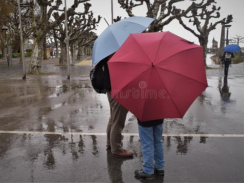 Man and boy are waiting about during rainy day in city of Konstanz, Germany. The man has a blue umbrella and black rucksack. The boy has red umbrella and blue stock photography