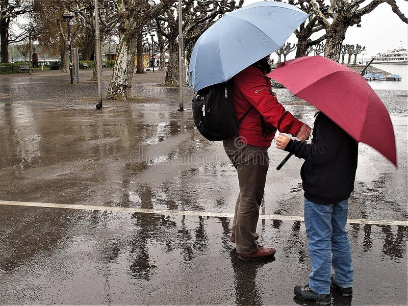 Man and boy are walking during rainy day in city of Konstanz, Germany. The man has a blue umbrella, red anorak and black rucksack. The boy has red umbrella and stock photography
