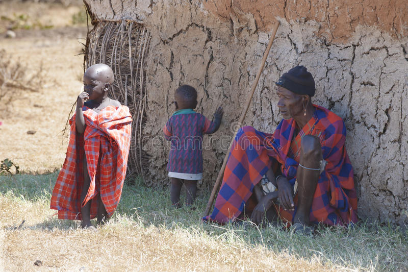 Maasai People, Tanzania, Boys and Man of the Masai Tribe in front of hut. royalty free stock images