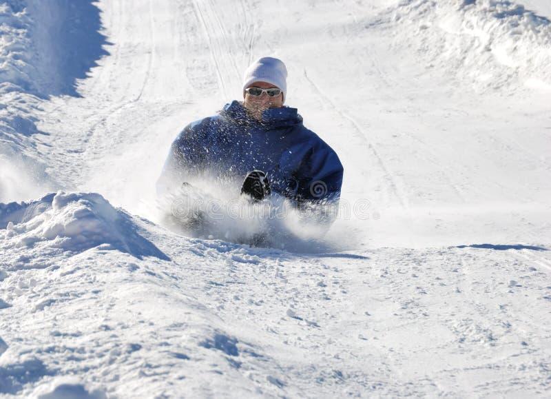 Man Braking While Sledding Down The Hill Stock Photo