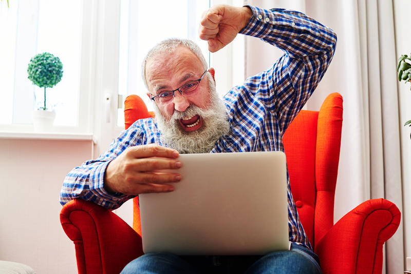 Man brandishing his fist and screaming. Emotional senior man brandishing his fist and screaming at laptop at home royalty free stock images