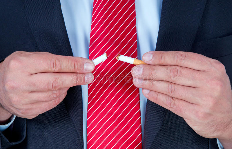Man Breaking Cigarette in Two. Businessman in suit and tie breaking a cigarette in half. Stop smoking stock photography