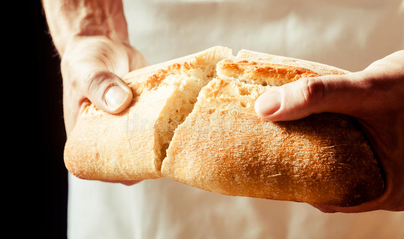 Man breaking a loaf of crusty white bread. Man breaking a loaf of crusty freshly baked white bread with his hands as he prepares to enjoy a lunchtime snack royalty free stock image