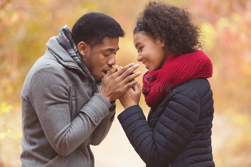 Man with breath warming woman hands in park royalty free stock image