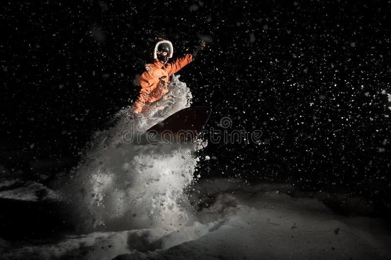 Man breathtakingly snowboardingen på natten under snön fotografering för bildbyråer