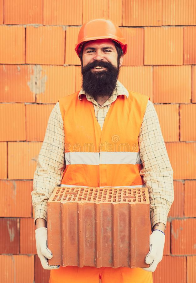 Man with brick on orange wall construction background. Construction builder worker at building site. stock photography