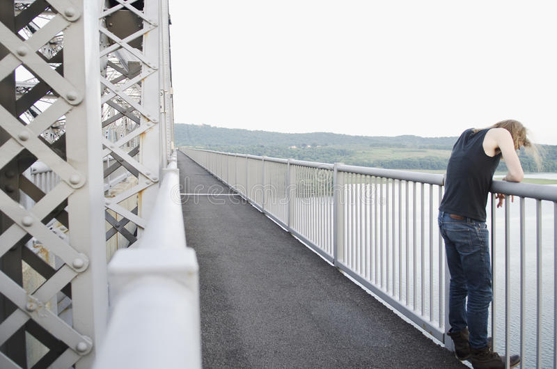 Man on bridge contemplating suicide royalty free stock photo