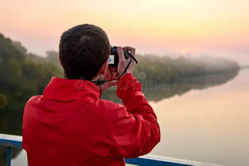 A man on a bridge over the river that photographs a sunrise on a foggy morning. A man on a bridge over the river that photographs a sunrise on a foggy early royalty free stock image