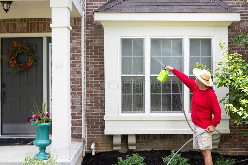 Man washing the bump-out or bay windows. Man in a bright red top washing the exterior bump-out or bay windows on a brick house using a handheld pressure sprayer royalty free stock image
