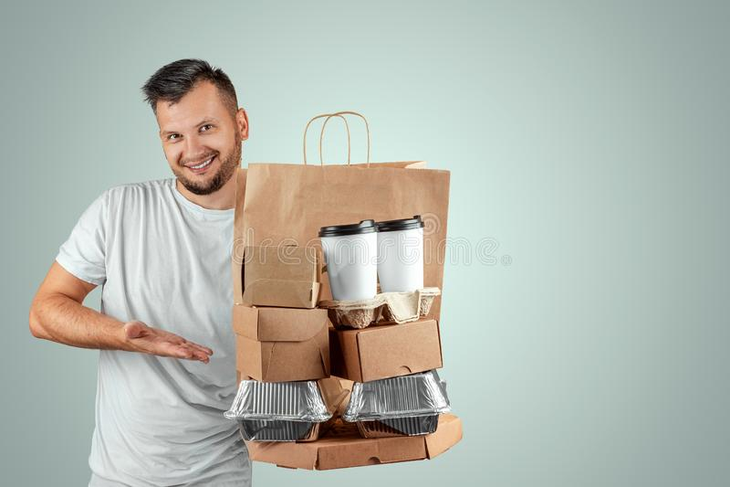 Man in a bright T-shirt giving a fast food order isolated on a blue background. Male courier worker is holding food. Home delivery. Of goods from a store or stock photography