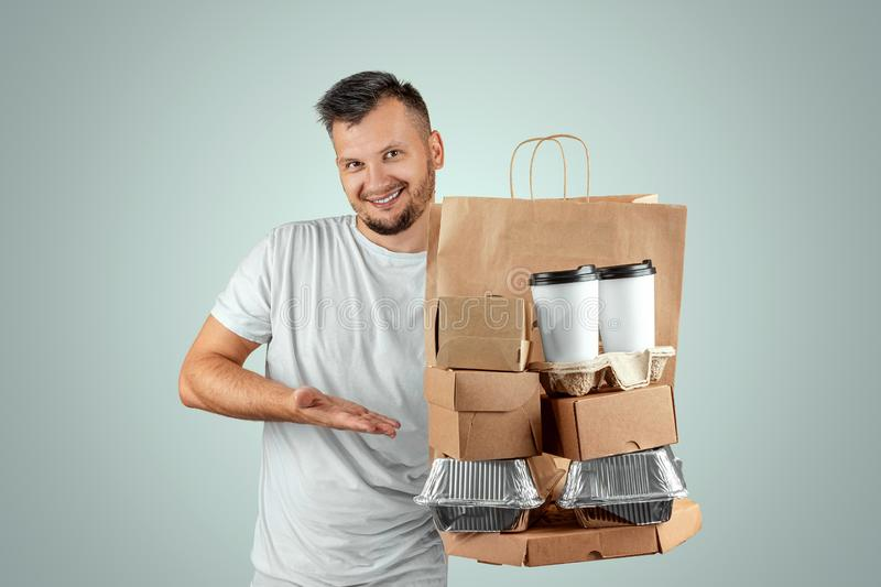 Man in a bright T-shirt giving a fast food order isolated on a blue background. Male courier worker is holding food. Home delivery. Of goods from a store or royalty free stock images
